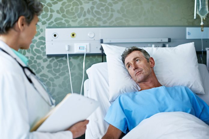 doctor talking to a patient who is in a hospital bed