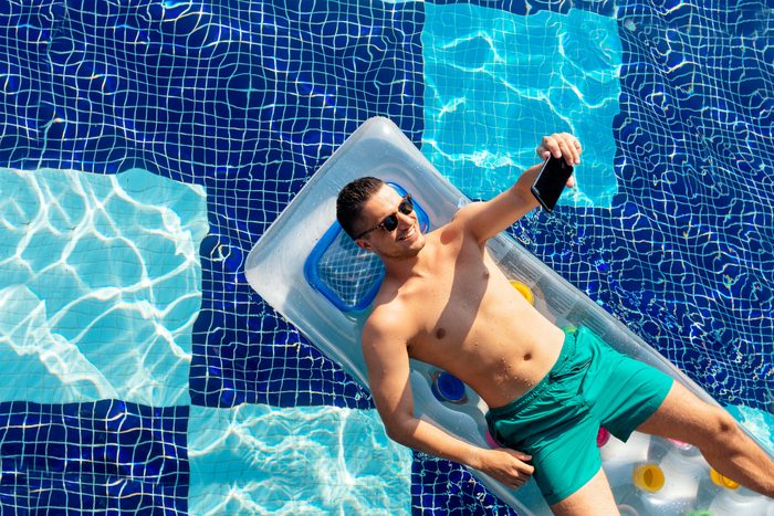 man taking a selfie picture while laying on pool float