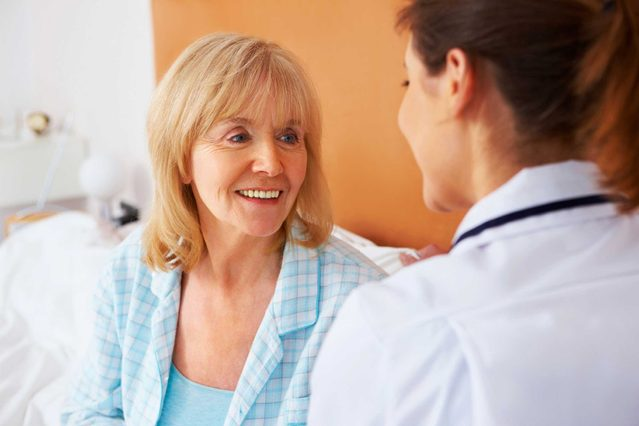 Woman doctor talking to an elderly female patient