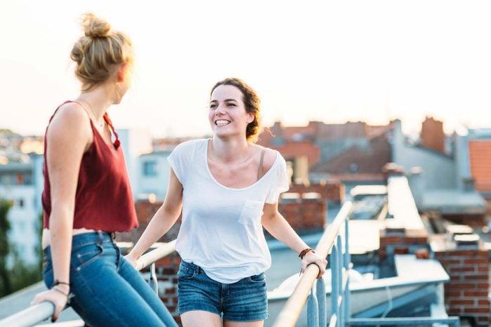 two women talking on a rooftop