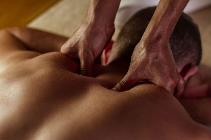 close-up of hands massaging a man's upper back