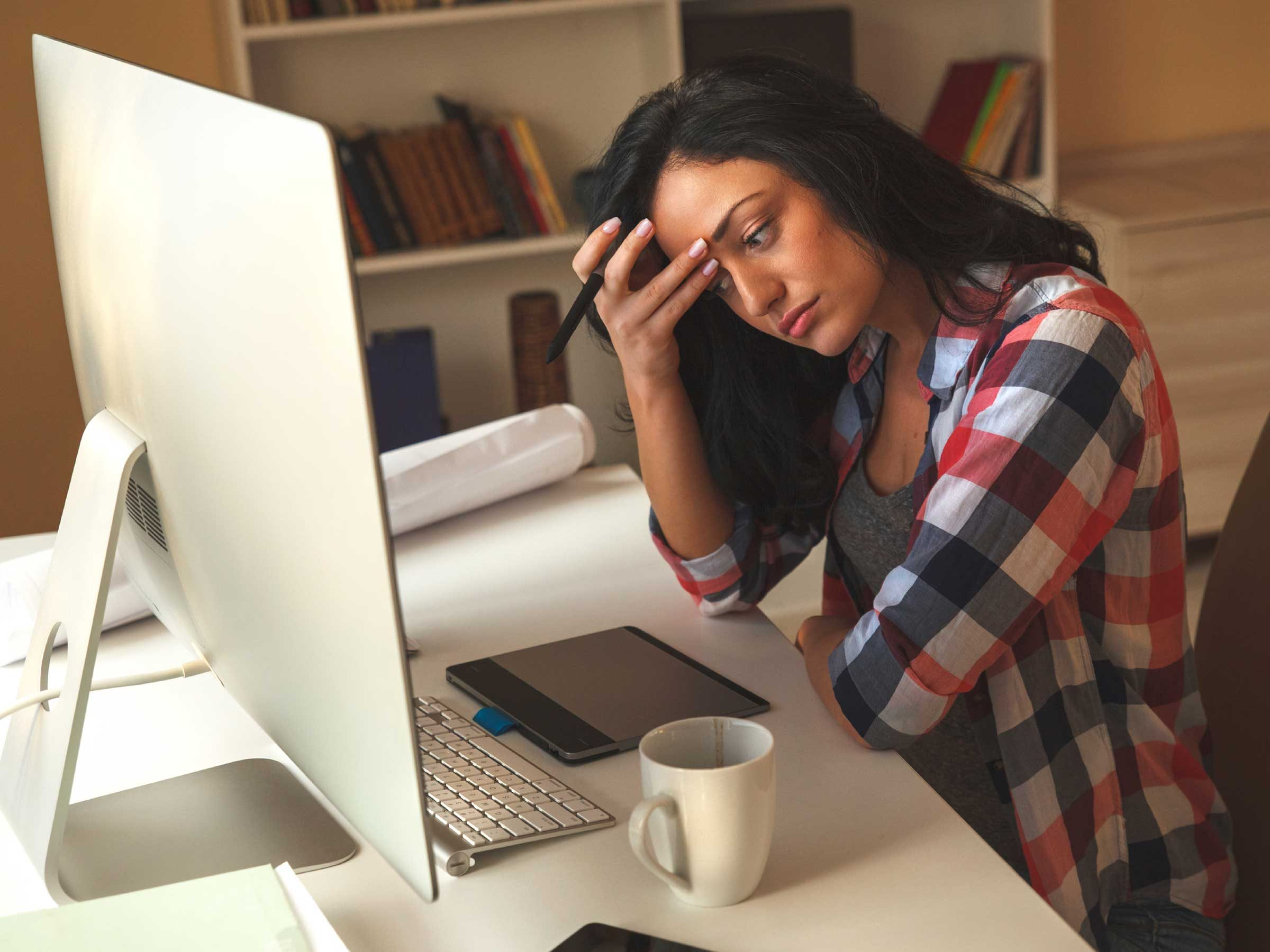 woman looking stressed in front of a computer monitor