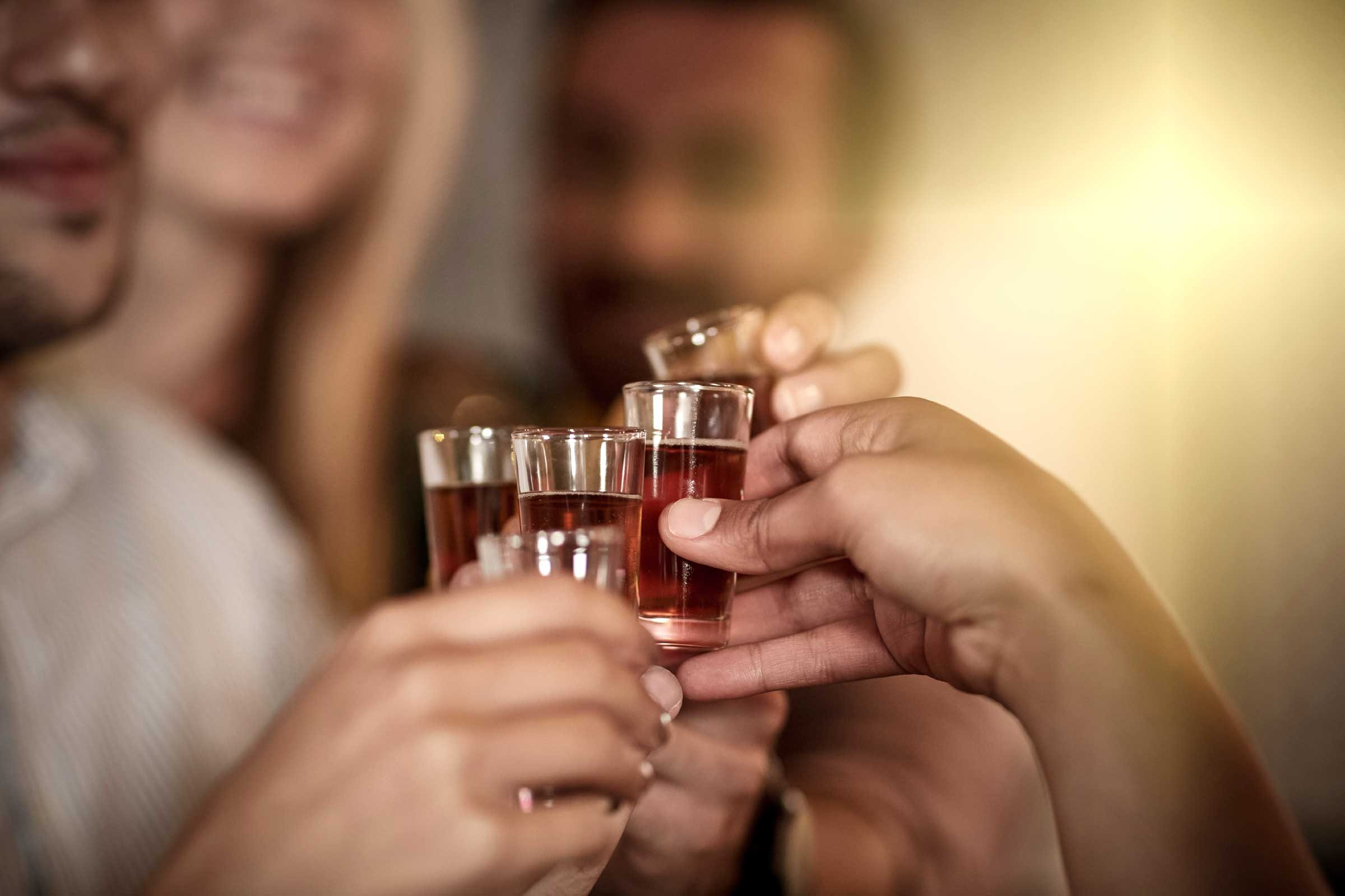 closeup of hands holding shot glasses