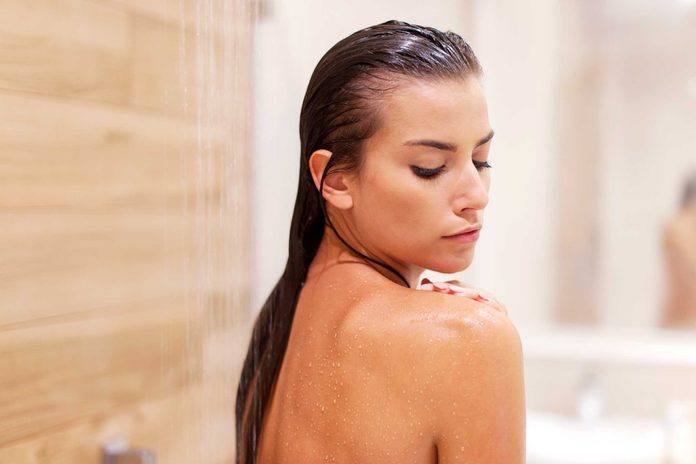 bathing dark-haired woman looking over her shoulder