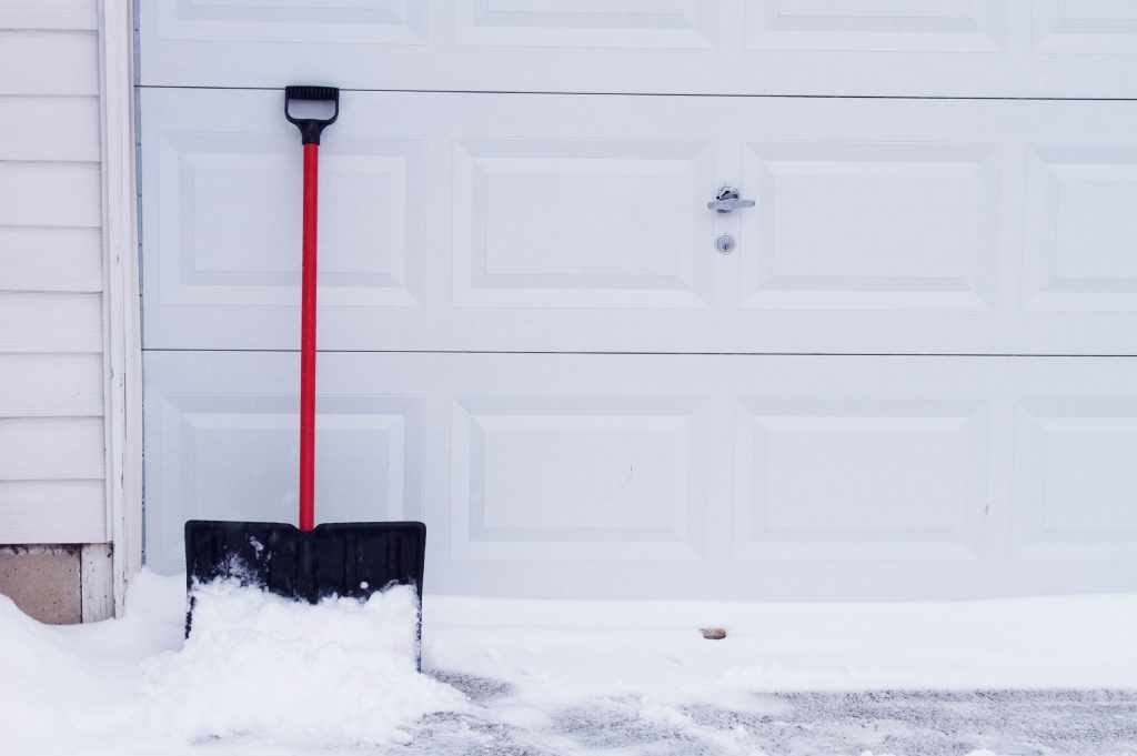 snow shovel leaning against garage door