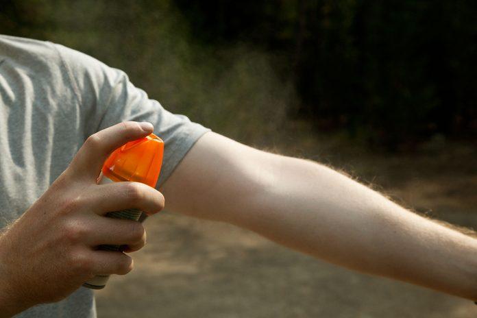 person spraying bug spray on arm