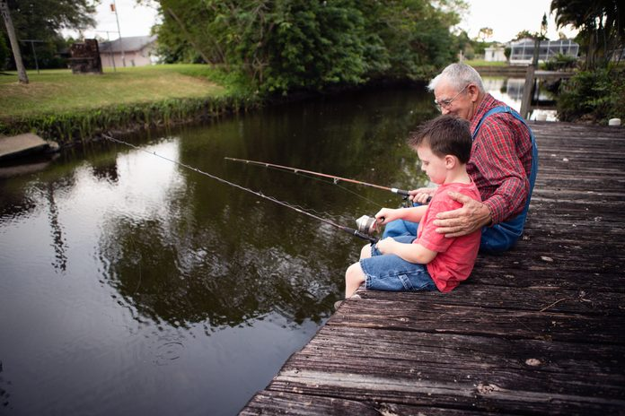 older man and boy fishing off a dock