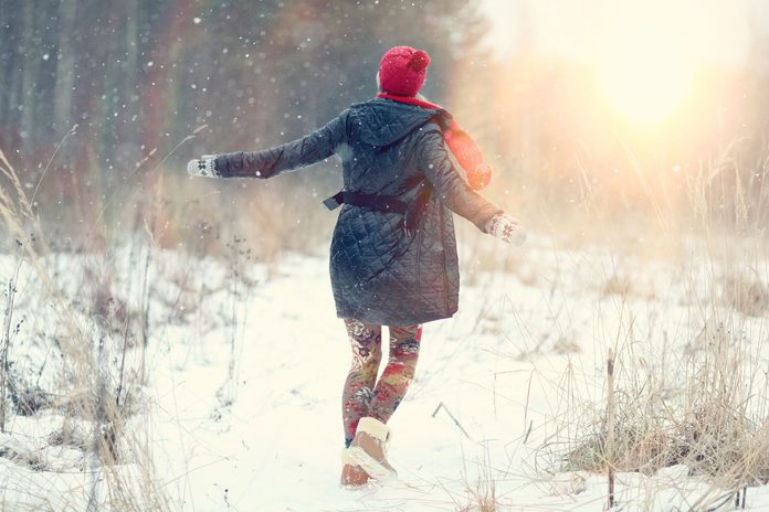 woman in coat and hat walking in a snowy field