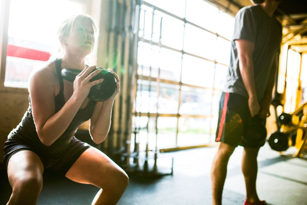 man and woman lifting kettlebells in a gym