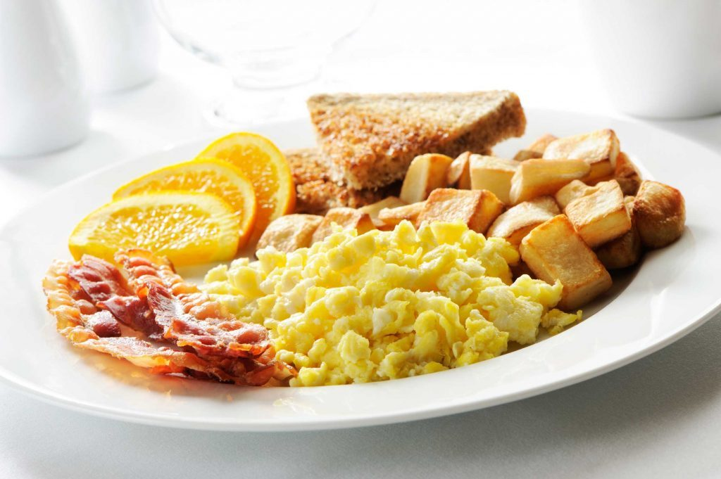 plate of eggs, bacon, hash browns, toast, and orange slices