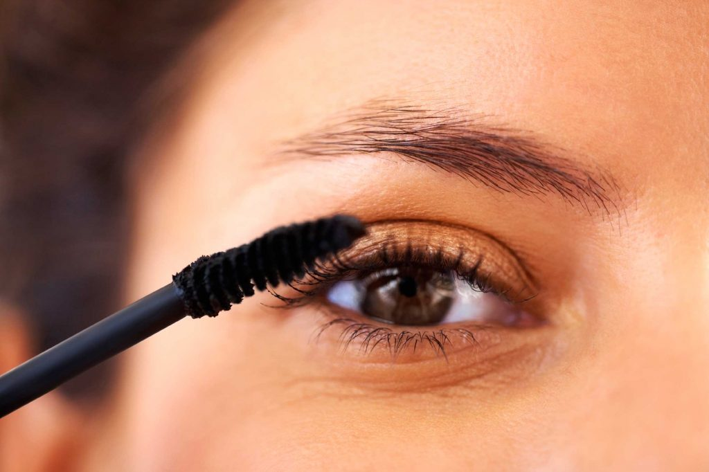 Woman applying mascara to her eyelashes.