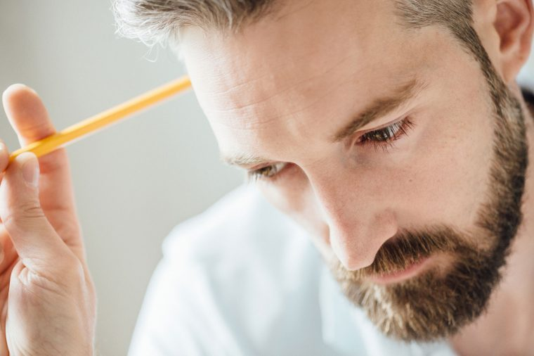 Man with a beard holding a pencil in his hand, as if he's having trouble concentrating.