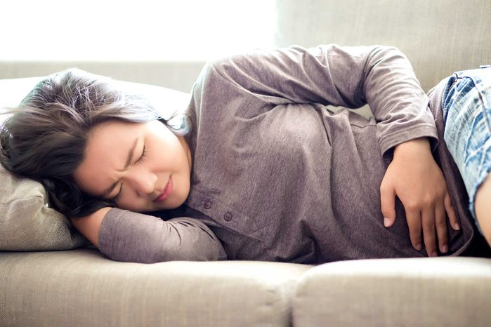 Woman on her side holding her stomach in pain