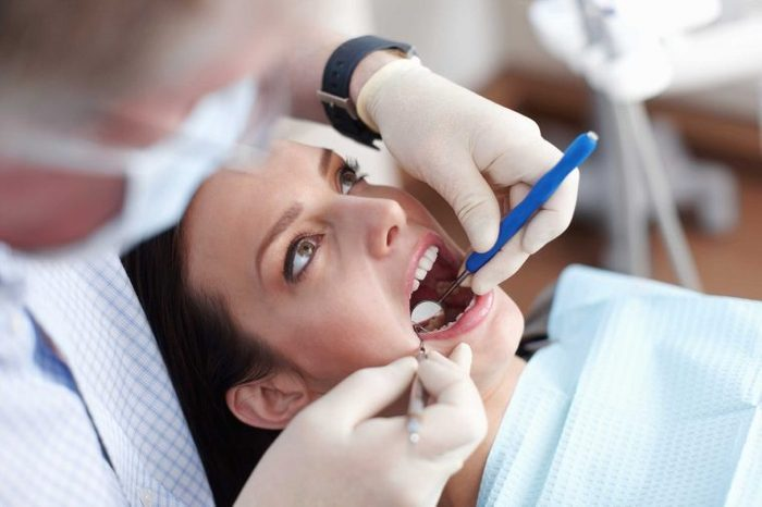 Woman dental patient opening her mouth while her dentist inspects her teeth with a hand mirror.