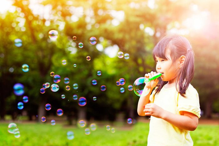 Young girl blowing soap bubbles outside.