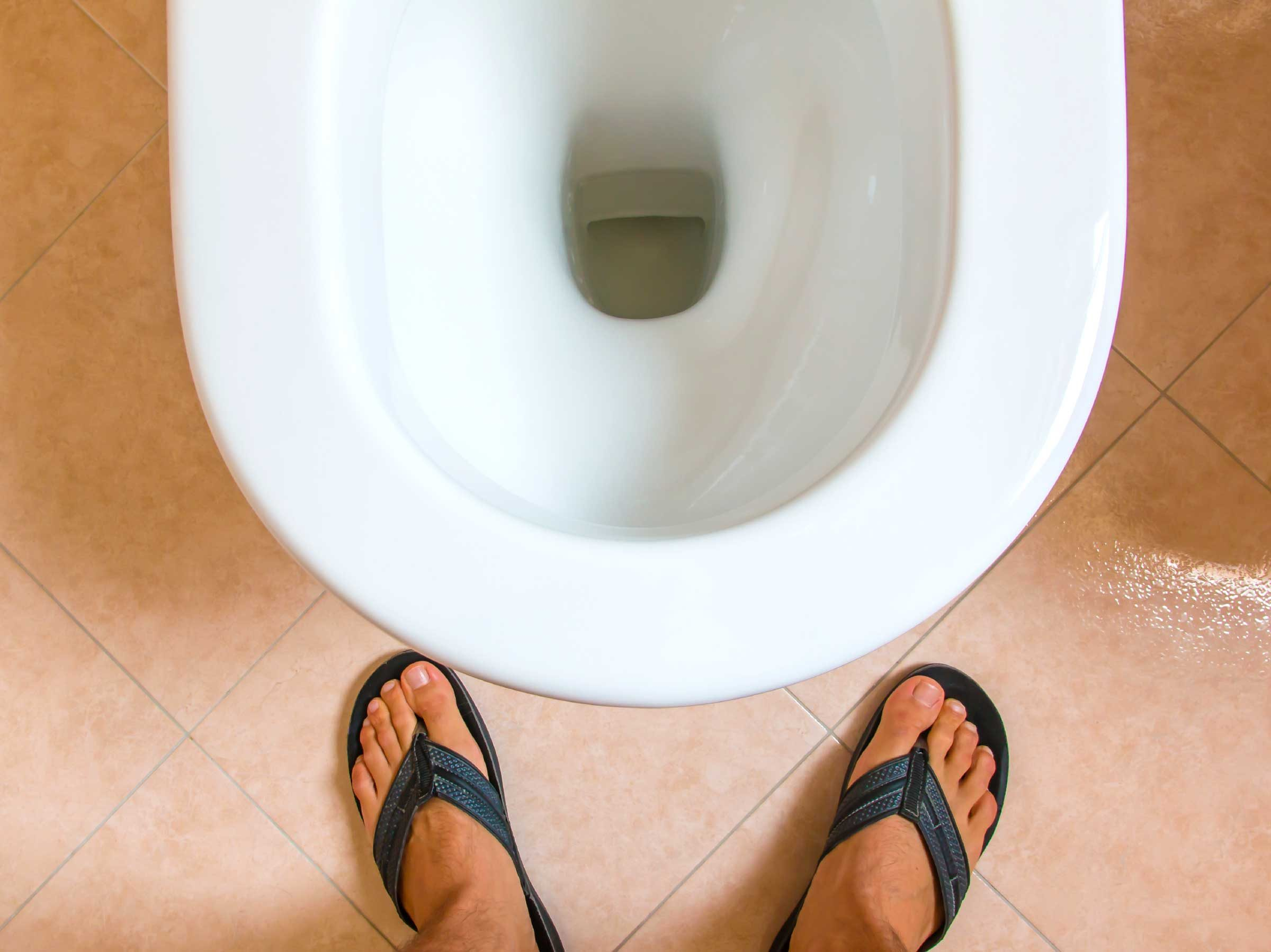 man's feet in front of a toilet