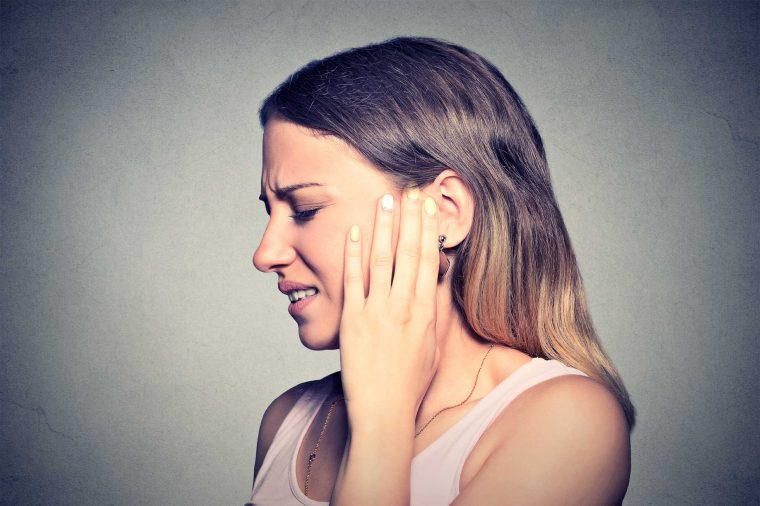 A woman turned to the side, holding up her left hand to her left ear as if it's causing her pain.