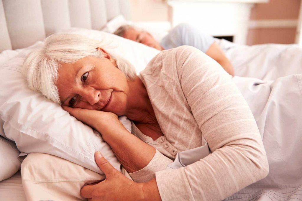awake woman on side in bed next to a man