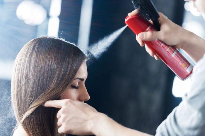 Woman with brown hair getting her hair done (and hair sprayed) at the salon.