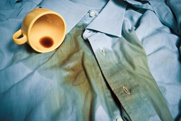 A coffee cup that has spilled coffee onto a blue button-down dress shirt.