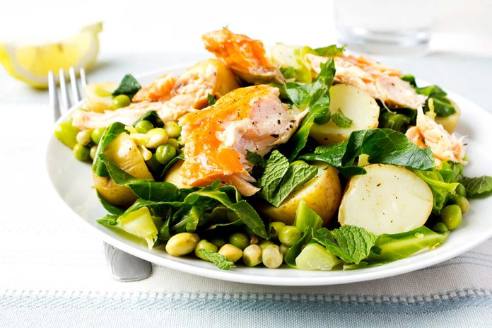 salmon on salad on white plate with fork