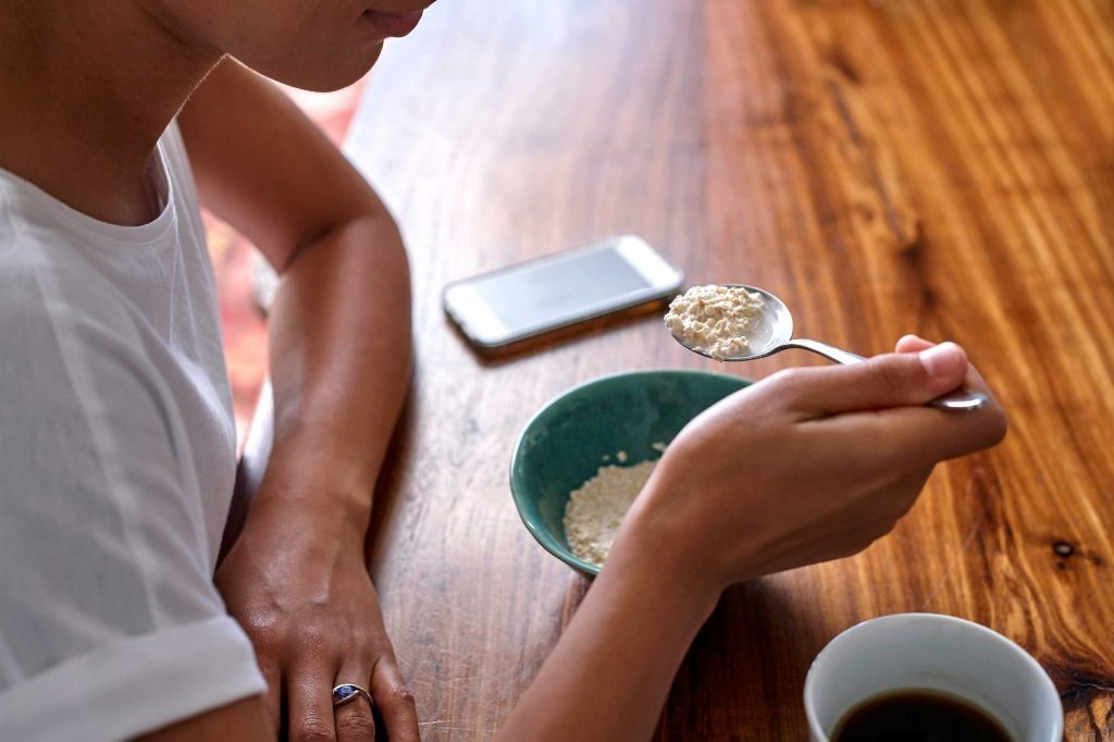 woman eating bowl of cereal at table with coffee and smartphone
