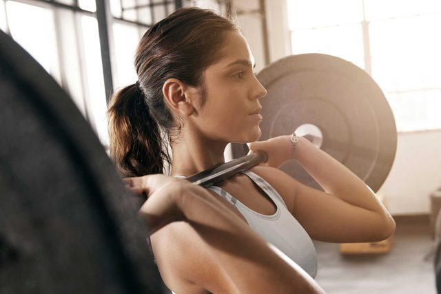 woman lifting barbell with heavy weights