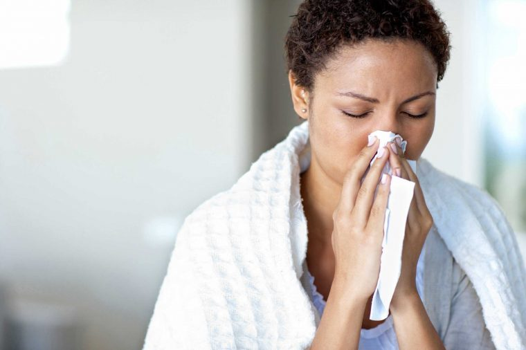 A woman wearing a white towel blowing her nose into a tissue.