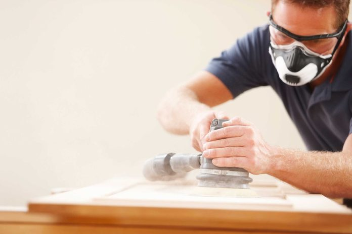 Man wearing goggles and face mask while sanding wood.