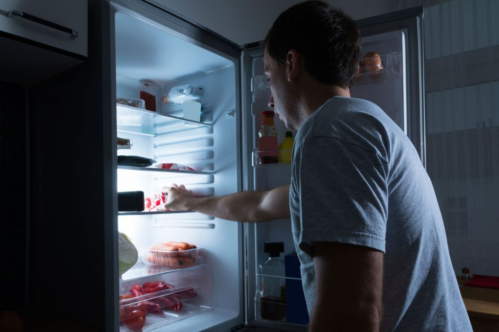 man looking into refrigerator at night