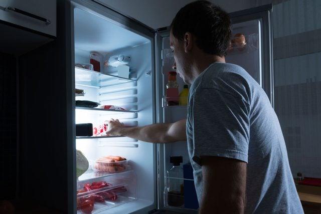 man looking into refrigerator at night