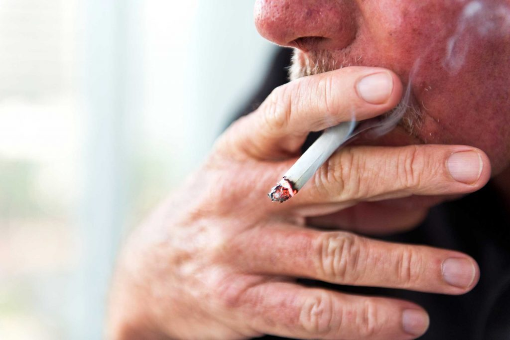 Male smoking a cigarette.