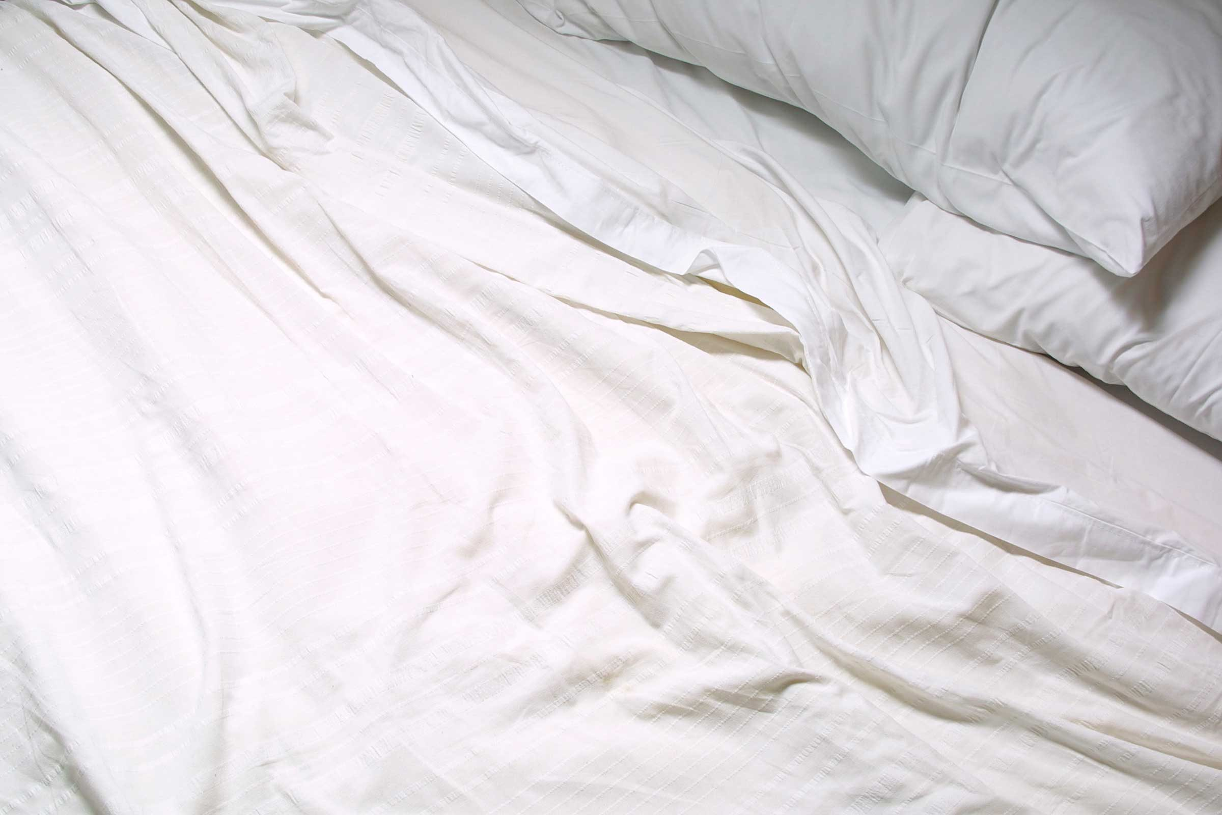 white sheets in unmade bed