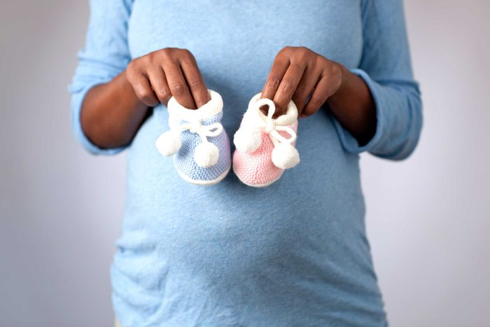 woman holding pink and blue baby booties