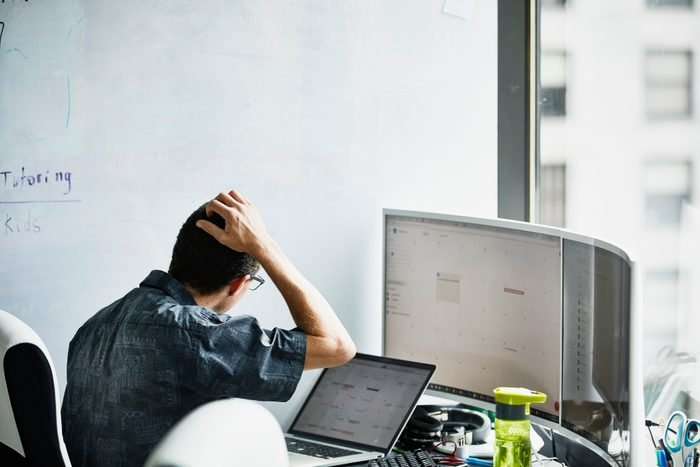man working and scratching his head while looking at computer