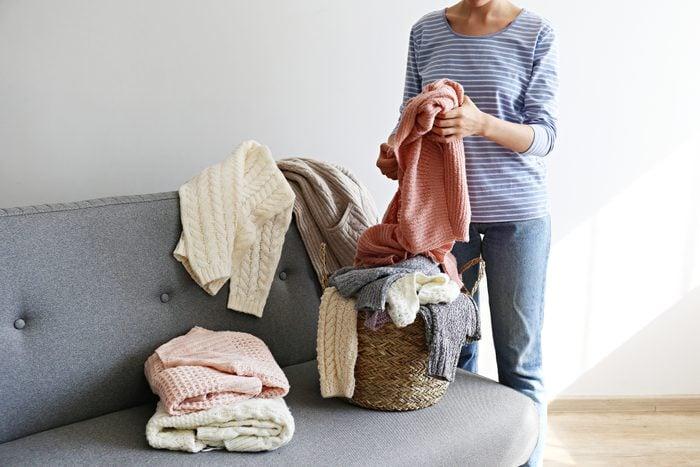 cropped shot of woman organizing laundry