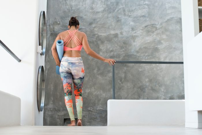 woman leaving yoga class with yoga mat in hand