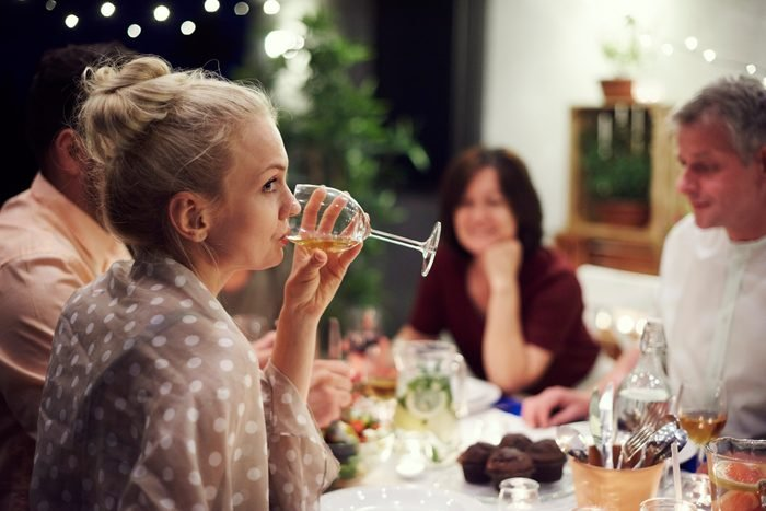 woman bored of conversation drinking wine at dinner table