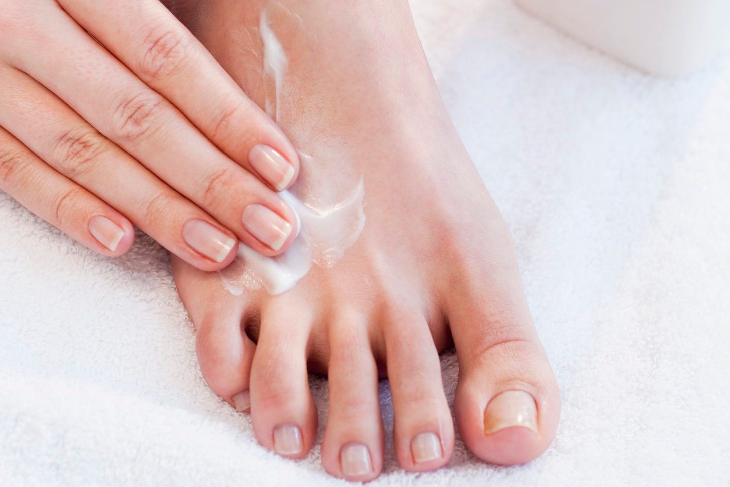 close up of woman applying lotion to foot