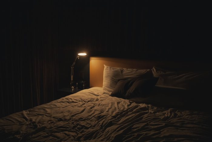 dark bedroom at night with table lamp on