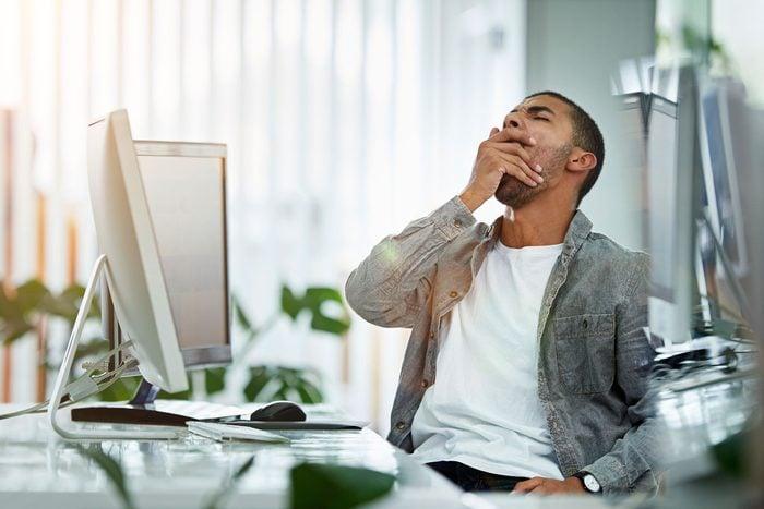 Man yawning while sitting at a desk