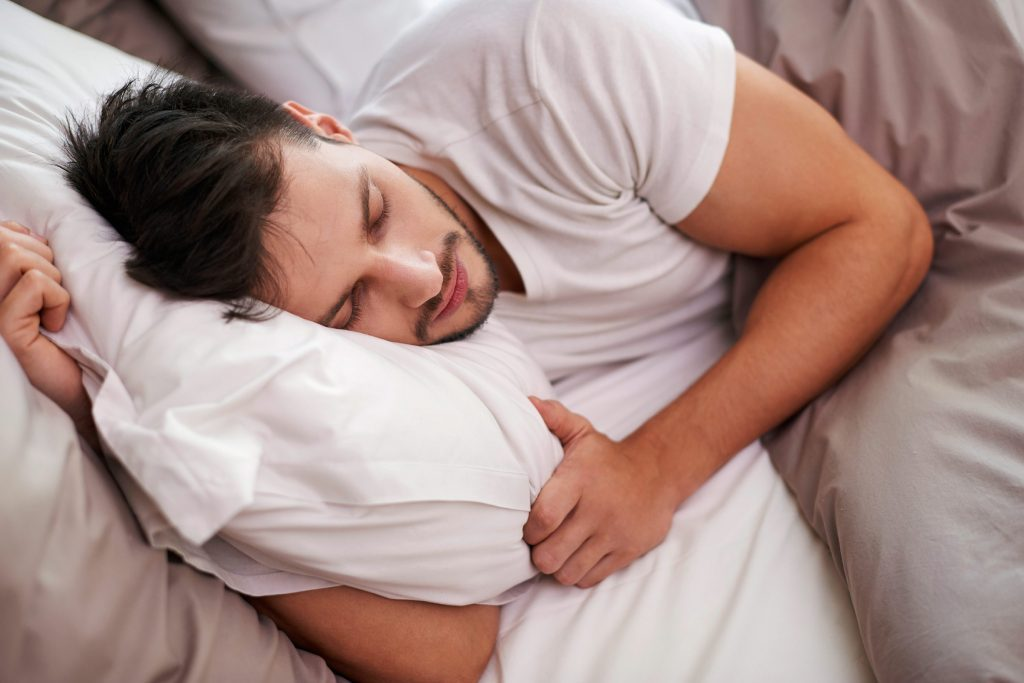 man snoozing on his side in bed