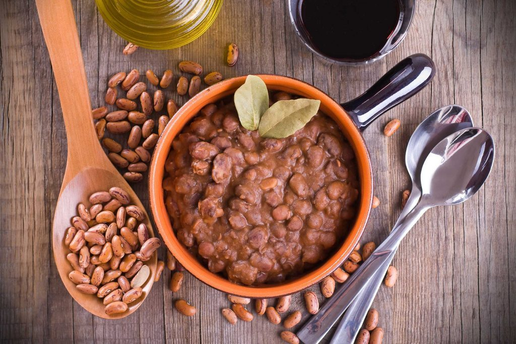 bowl of cooked beans with dry beans scattered on table