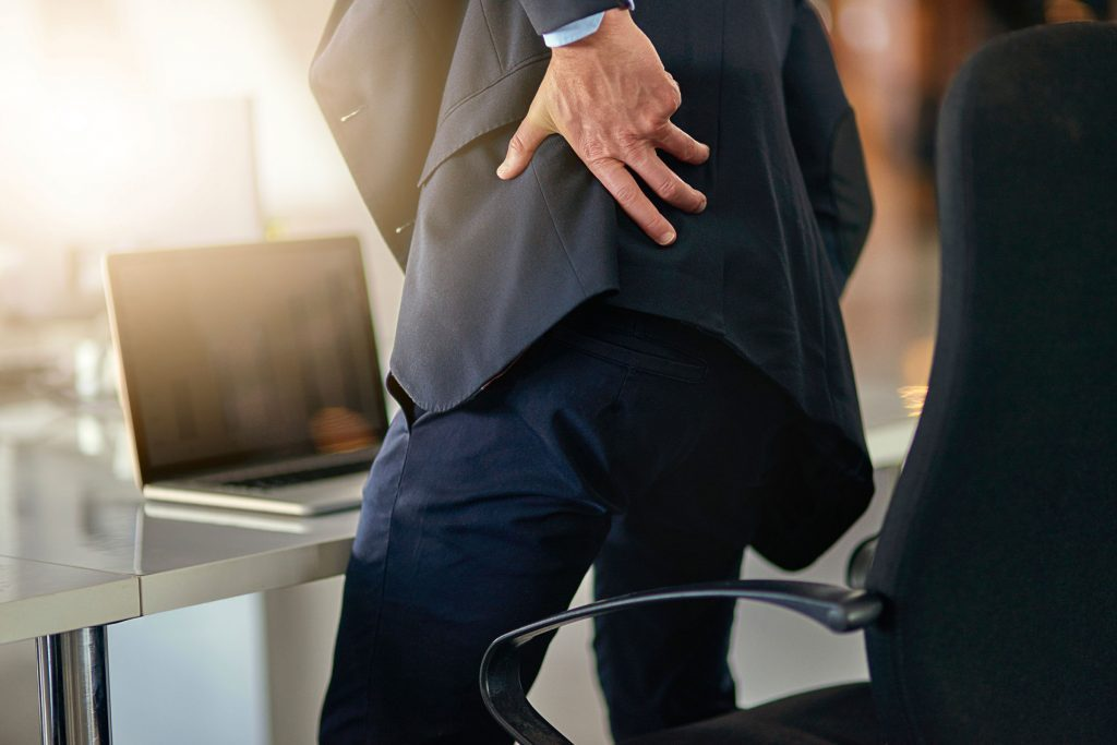 Man in a business suit standing up at his desk and reaching for his lower back in pain