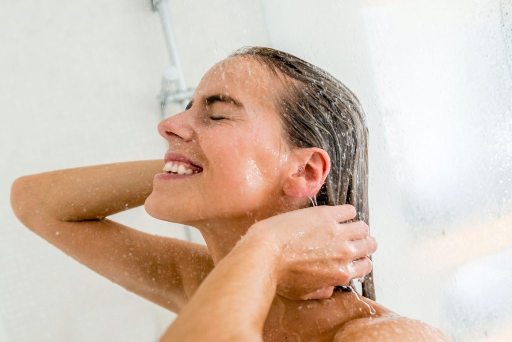 woman showering with eyes closed