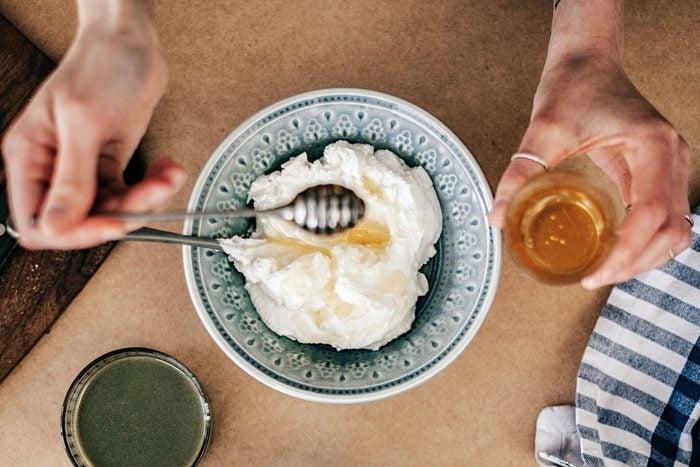 someone drizzling honey over yogurt