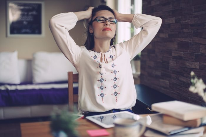 stressed woman at office desk, hands on head