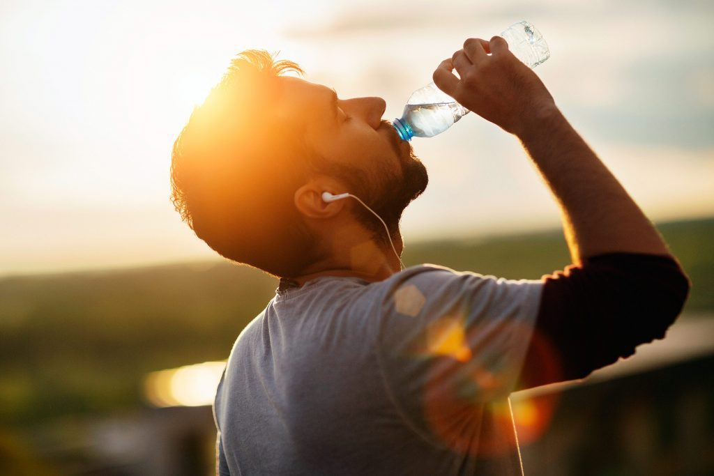man with earbuds outside, drinking from a bottle of water