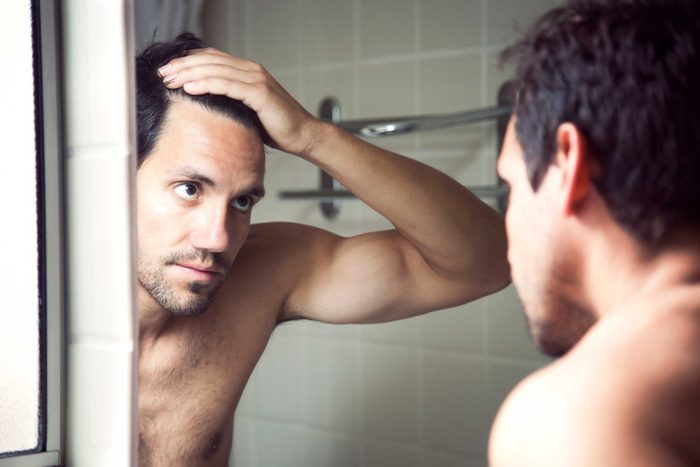 man looking at his hairline in a mirror