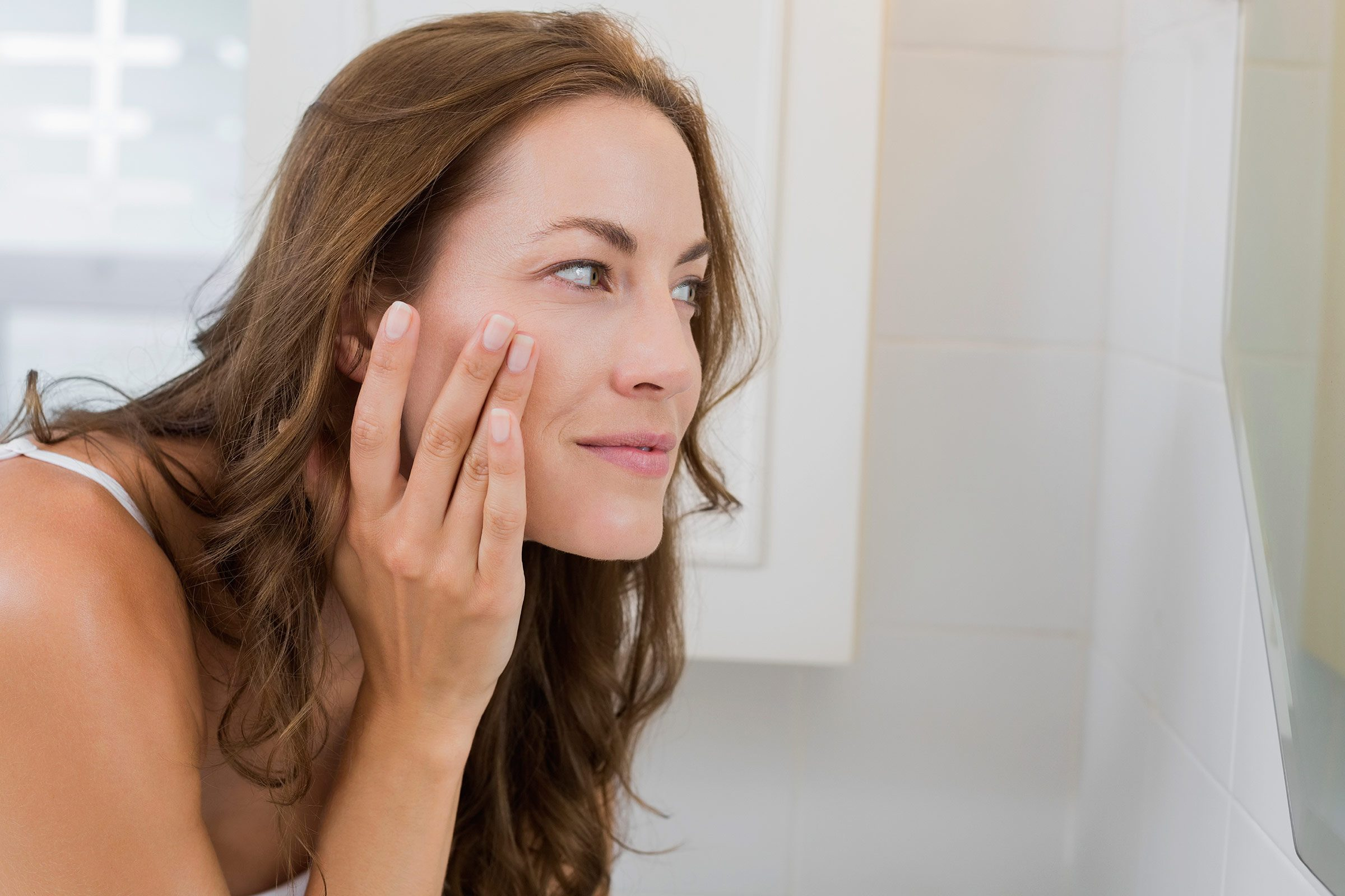 woman touching face and looking in the mirror